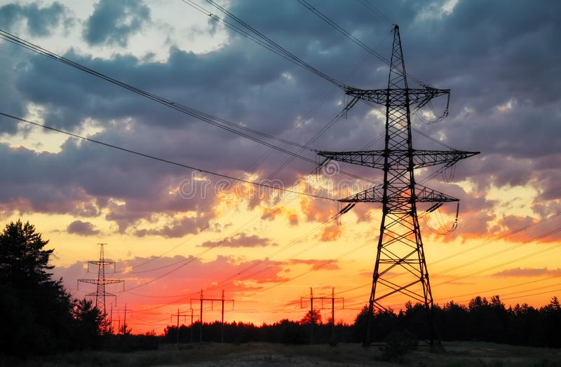 Silhouette High voltage electric towers at sunset time. High-voltage power lines. royalty free stock images