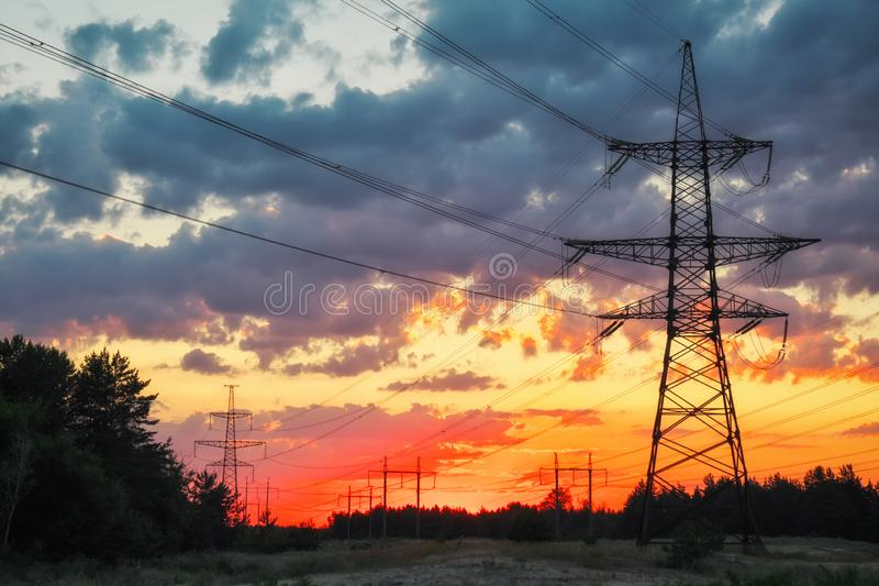 Silhouette High voltage electric towers at sunset time. High-voltage power lines stock image