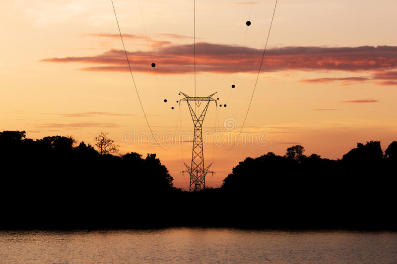 Silhouette high voltage post, power transmission tower at Sirindhorn Dam in the morning time.  stock photos
