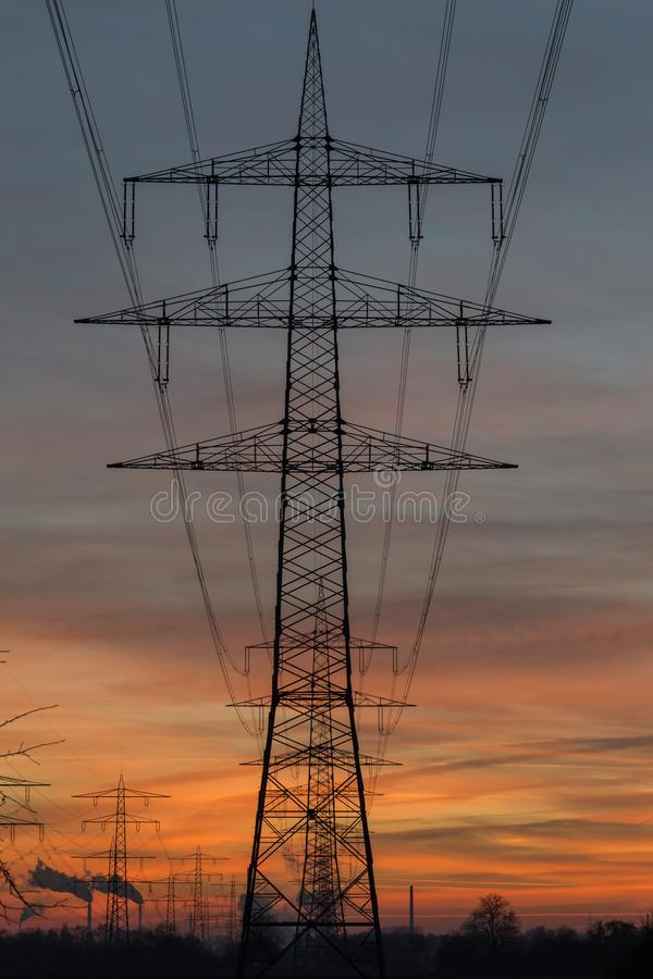 Silhouette of high voltage power lines against a sunset sky stock photo