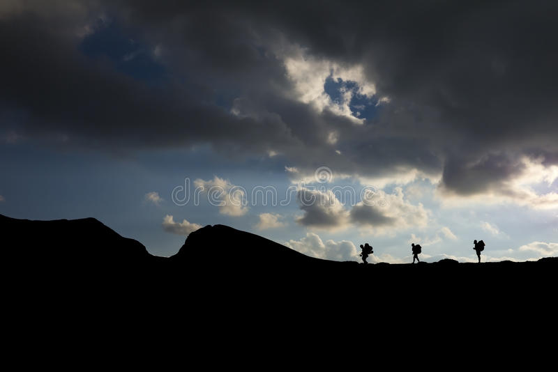 Silhouette of hikers with backpacks climbing the mountain. Silhouette of mountaineers hiking on the top of the mountain stock image