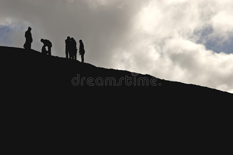 Silhouette of hikers on cliff, rock-climbing. Hiking, trekking - lots of copy space royalty free stock image