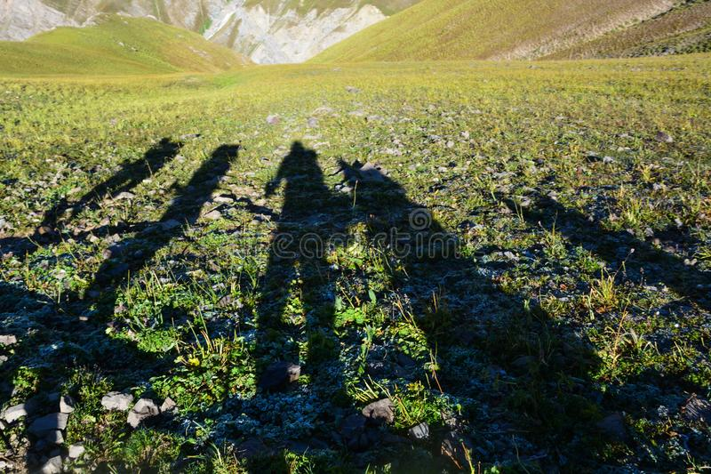 Silhouette of hikers on the grass. Mountain view. Distorted shadows of people stock image