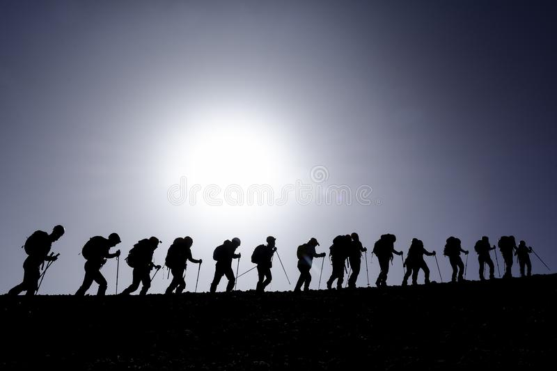 Silhouette of hikers on hill. Silhouette against blue skies of hikers with poles and backpacks on hill stock photography
