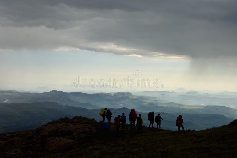 Silhouette of hikers looking at mountains and valleys. That are lighted up by the sun on a rainy day royalty free stock photography
