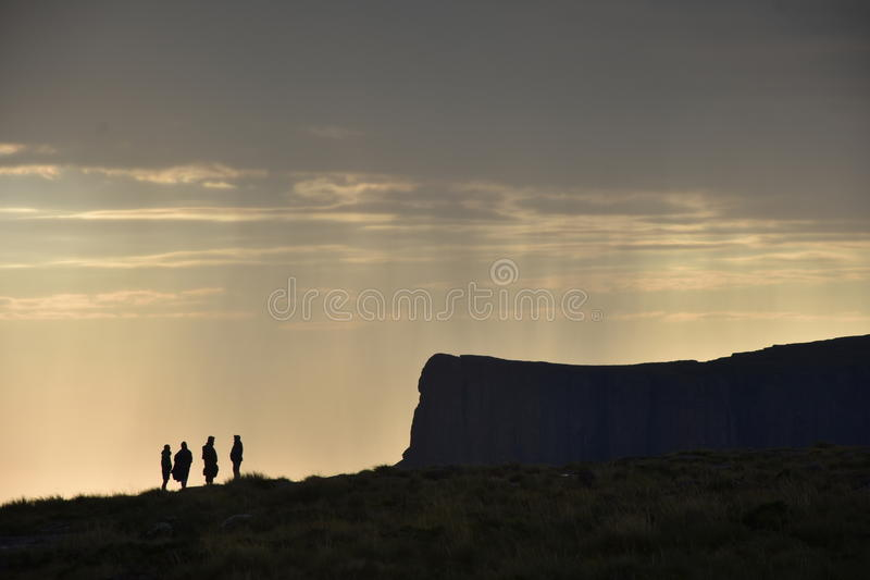 Silhouette Hikers on mountain. With rain in background stock photo