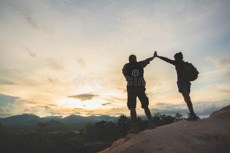 Silhouette of hikers standing on top of hill and enjoying sunrise over the valley, family, Couples, male and female, standing on. Top of the mountain royalty free stock photos
