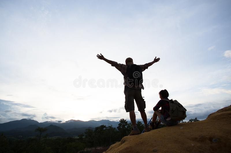 Silhouette of hikers standing on top of hill and enjoying sunrise over the valley stock image