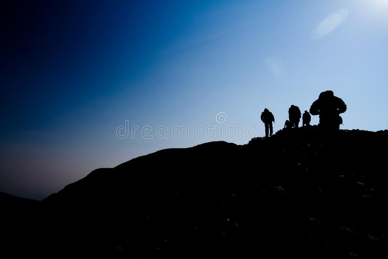 Silhouette of hikers walking up a mountain side. A group of hikers hiking up a mountain in the early morning, silhouetted by a rising sun royalty free stock photography