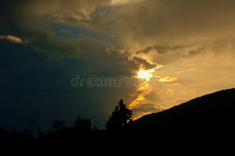 Silhouette of hill slope with trees under a cloudy sunset stock images
