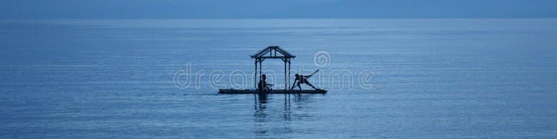 Silhouette-hommes sur le radeau en mer de la Chine photo stock