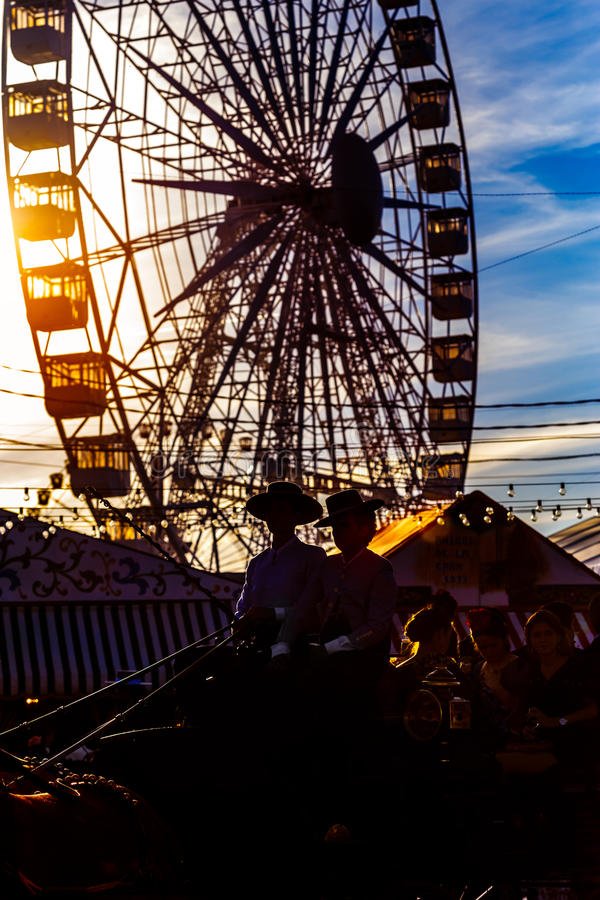 Silhouette of horse carriage and Ferris wheel at sunset. Seville`s April Fair. royalty free stock photo