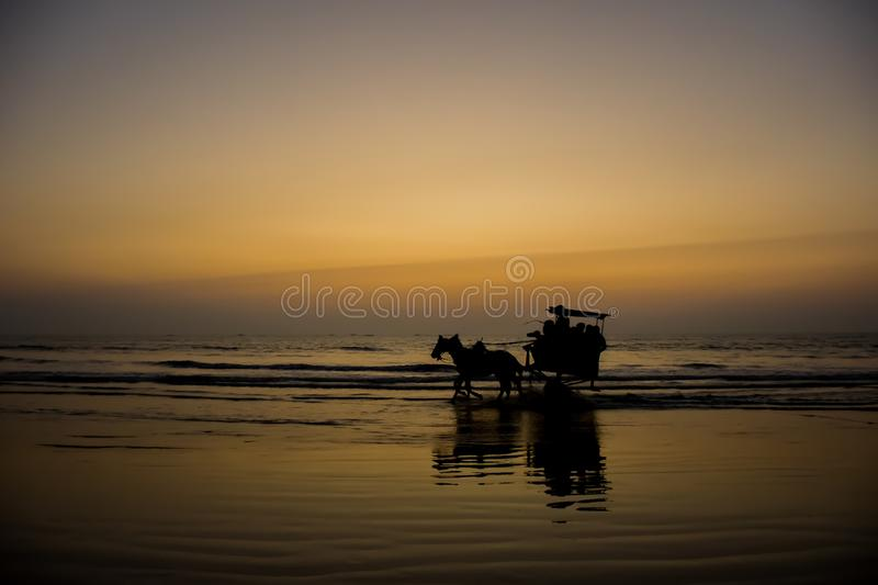 Silhouette of a horse cart running through water at a beach in India stock photos