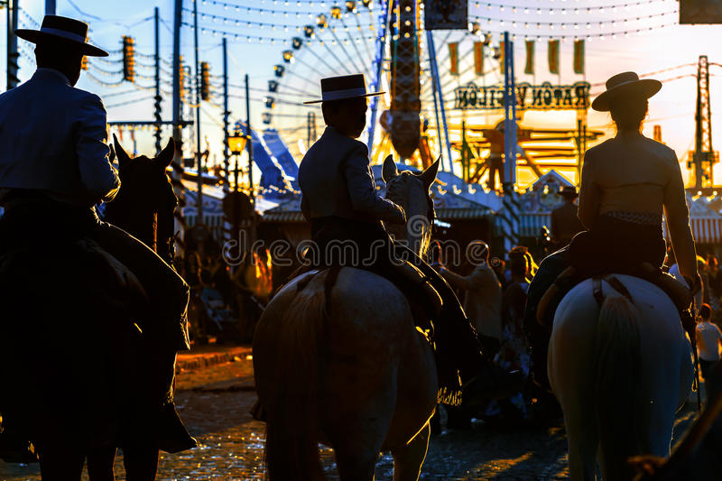 Silhouette of Horse riders at sunset. Seville`s April Fair. stock image
