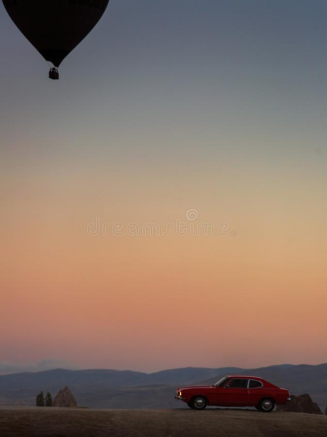 Silhouette of hot air balloons and an old red car in Cappadocia stock image