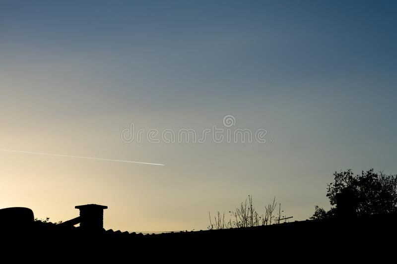Silhouette of house roof with blue and yellow sunset sky in background with airplane trail royalty free stock photos