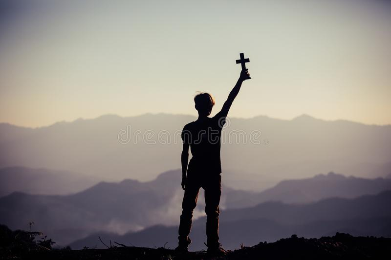 Silhouette of human hand holding cross, the background is the sunrise., Concept for Christian, stock images