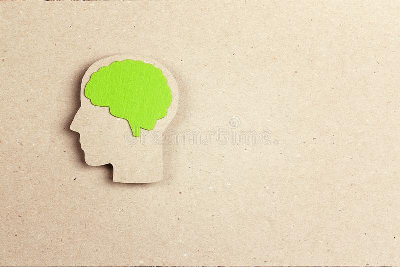 Silhouette human head with green brain on brown paper background royalty free stock photography