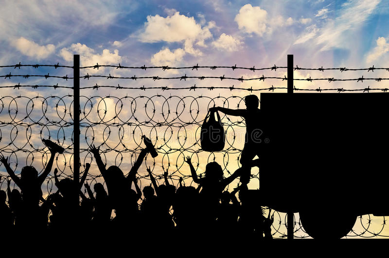Silhouette of humanitarian assistance to refugees. Concept of the refugees. Silhouette of humanitarian assistance to refugees near the fence with barbed wire stock image