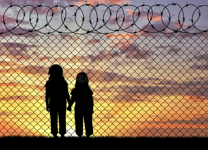 Silhouette of hungry children refugees. Concept of the refugees. Silhouette of hungry children in desperate refugees near the fence at sunset royalty free stock photos