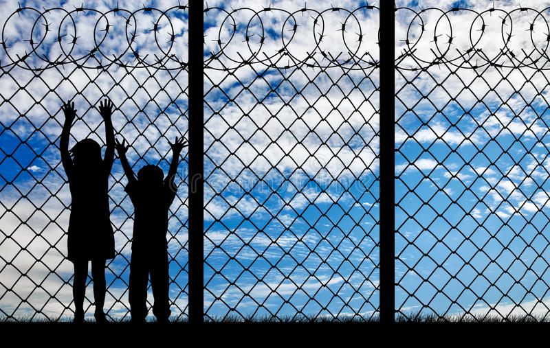 Silhouette hungry refugee children. Concept of refugee. Silhouette hungry refugee children near the fence with barbed wire royalty free stock images