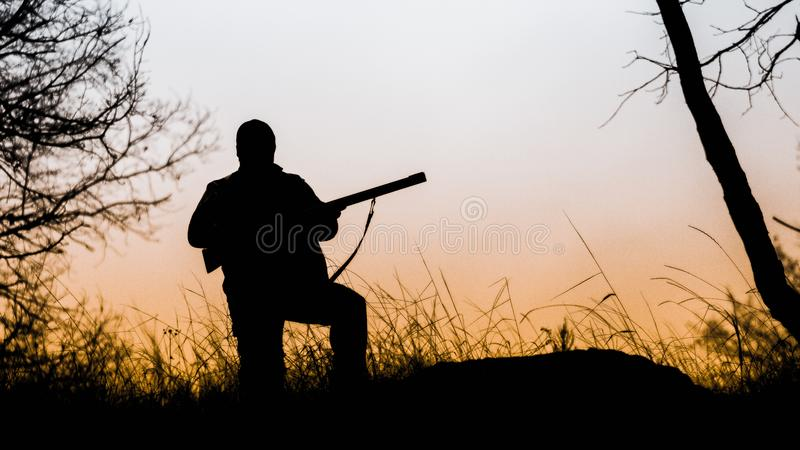 Silhouette of a hunter with a gun. Hunting stock image