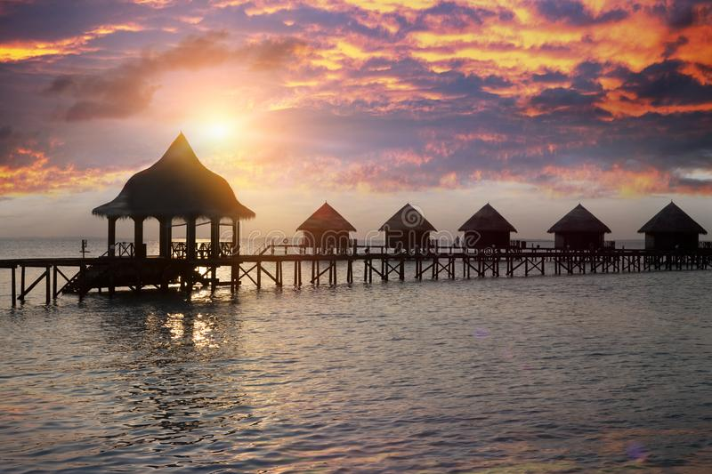 Silhouette hut over the transparent quiet sea water on a sunset. Maldives stock images