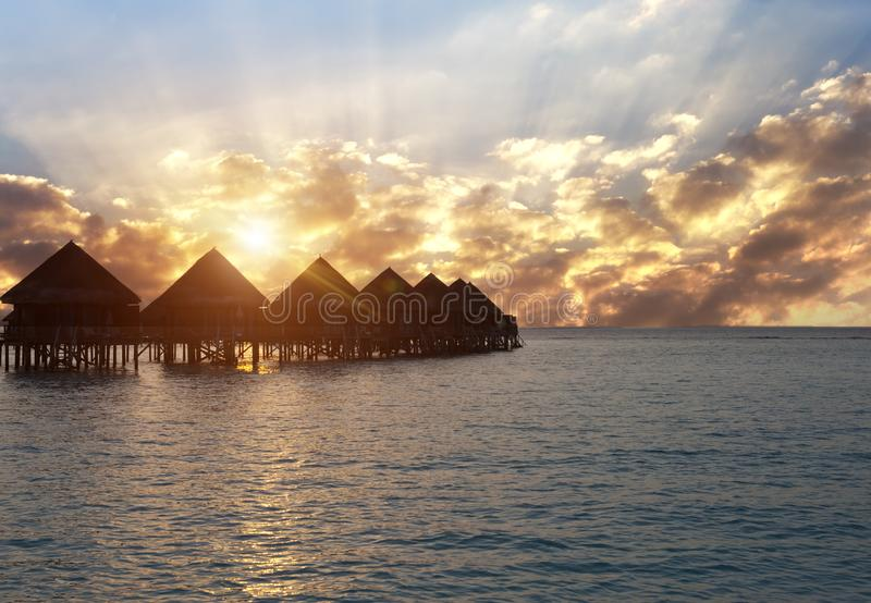 Silhouette hut over the transparent quiet sea water on a sunset. Maldives stock photography