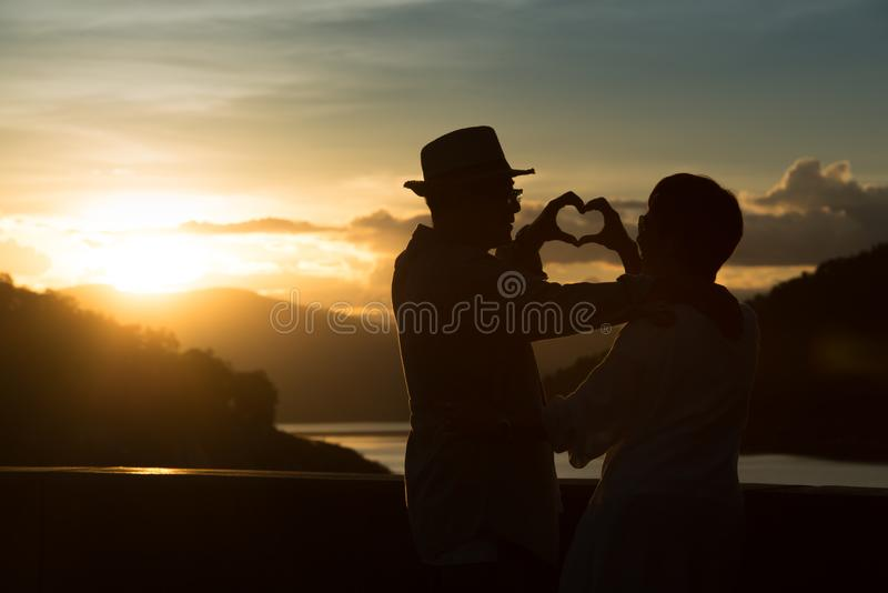 Silhouette of image of happy romantic senior couple making heart shape with hands outdoor at sunset background royalty free stock photos