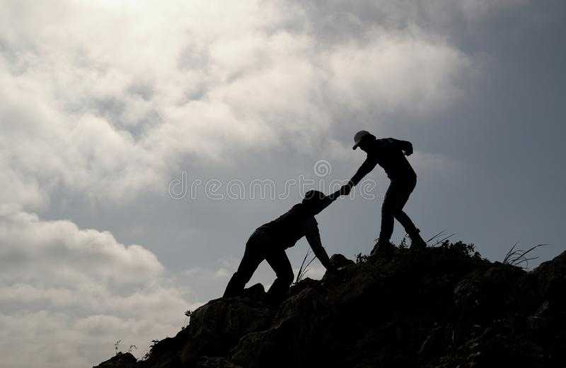 Silhouette image of one friend try to pull his other friend over the cliff of mountain and they climb and help each other during royalty free stock photography