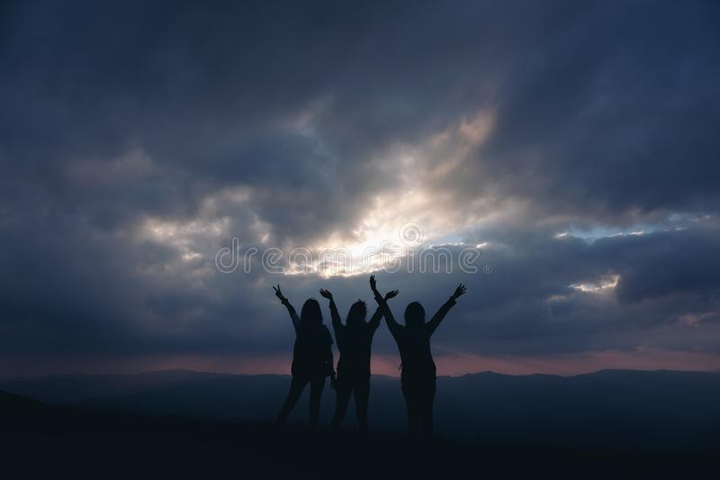 three women standing and raising hands, watching sunset with mountains view stock photos