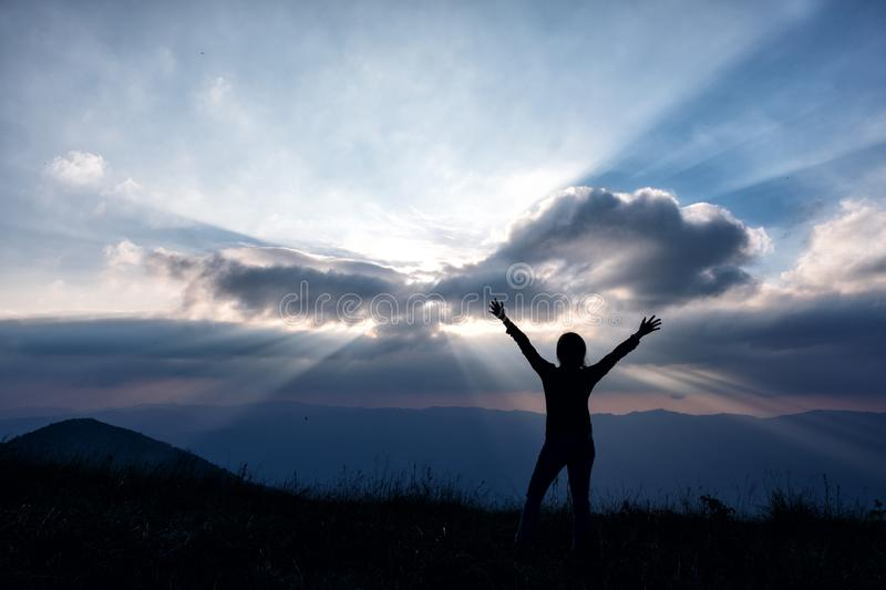 A woman standing and raising hands, watching sunset with mountains view royalty free stock photo