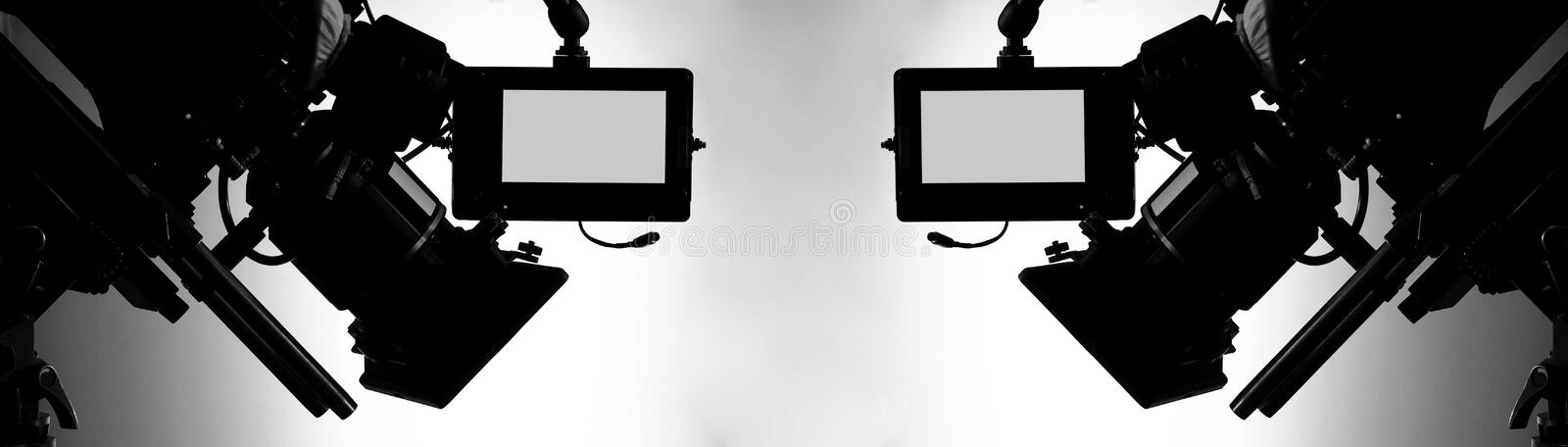 Silhouette images of video camera in tv commercial studio production. Which operating or shooting by cameraman and film crew team in set and prop on stock photography