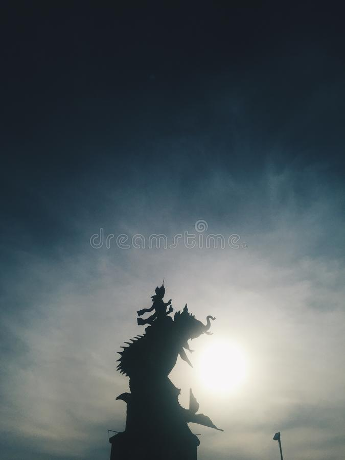 Silhouette of Indonesian statue at blue sky at background at sunset stock image