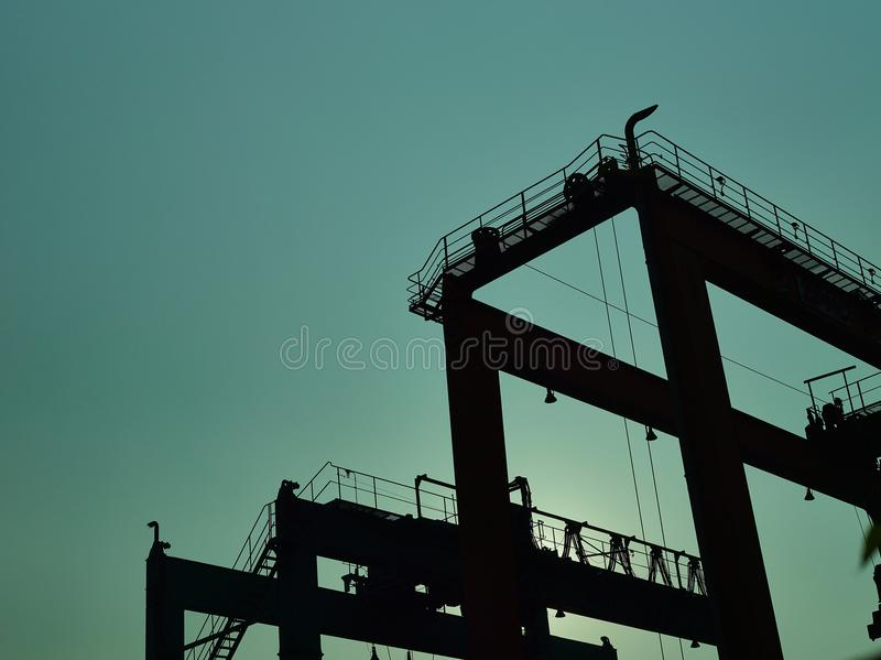 Gantry crane silhouette. The silhouette of an industrial gantry crane against the sky stock photos