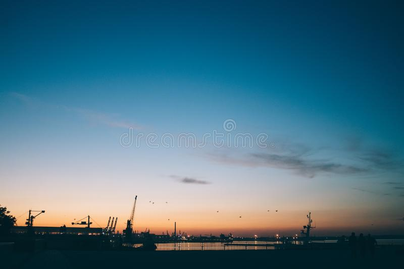 Silhouette industrial port against blue and orange sunset sky. Beautiful mood city landscape with urban lights and cargo cranes on sea stock photos