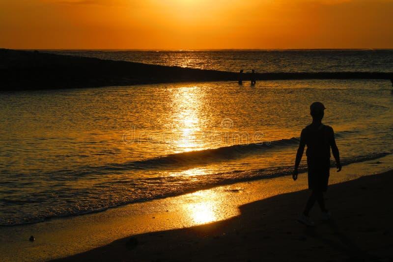 Silhouette jaune de coucher du soleil ou de lever de soleil de Bali de la marche de l'homme photographie stock