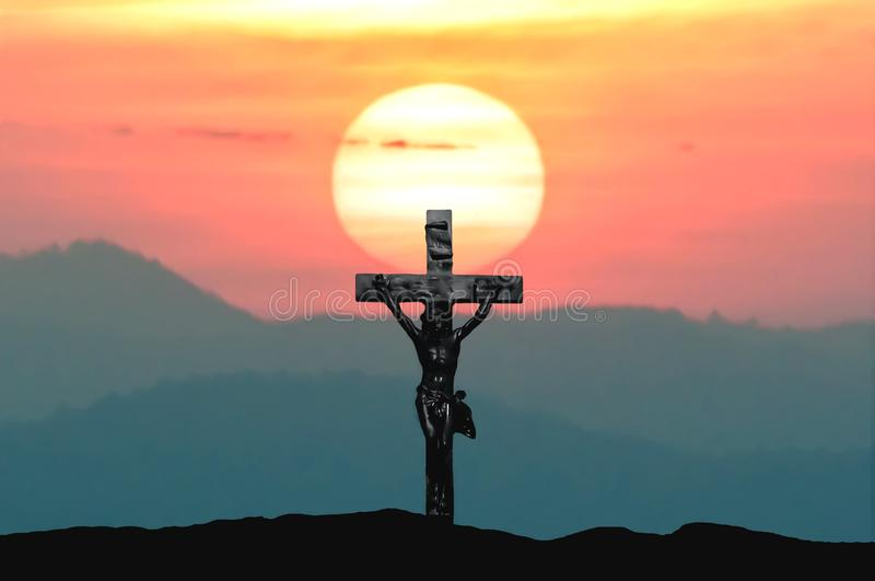 Silhouette Jesus and cross over sunset on mountain top with copy space royalty free stock image