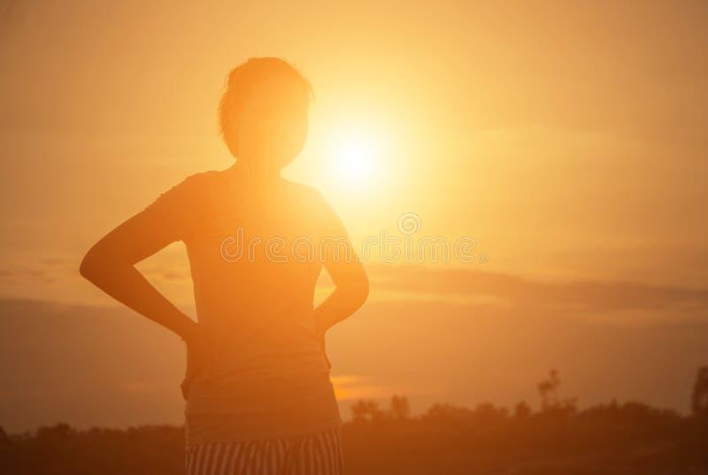 Silhouette jeune femme au coucher du soleil image stock
