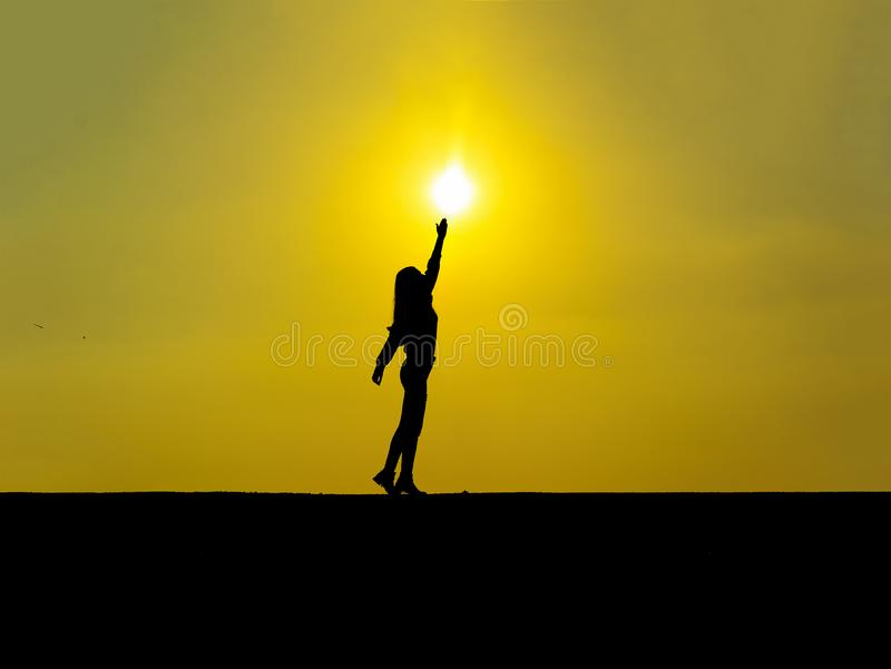 Silhouette-jeune fille touchant le soleil au coucher du soleil photographie stock libre de droits