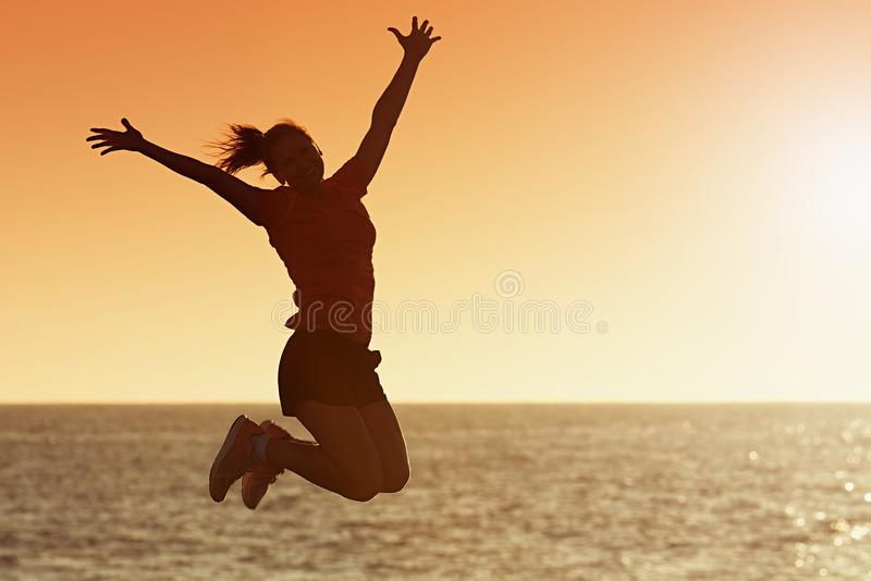 Silhouette of joyful woman jumping and having fun at the beach against the sunset royalty free stock image