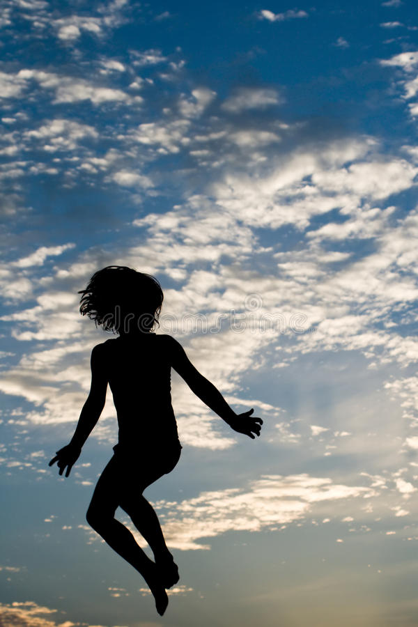 Silhouette Jump. Child silhouette jumping against sky royalty free stock photo