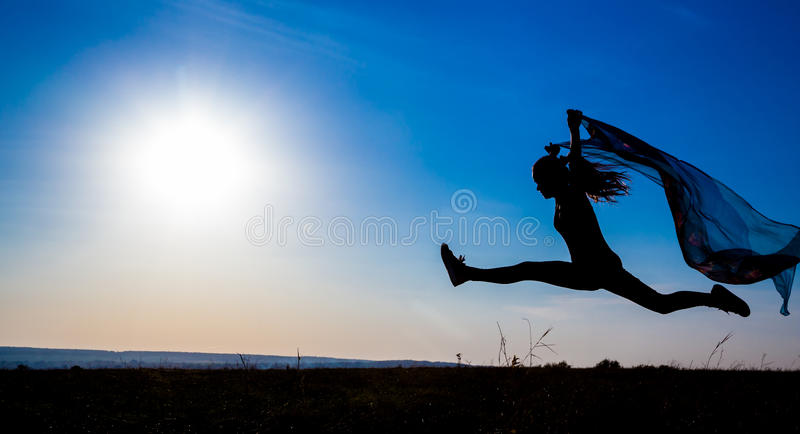 Silhouette of jumping girl against sunrise royalty free stock photos
