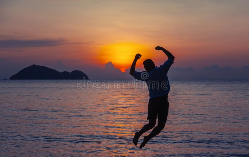 Silhouette of a jumping man on the seashore at sunset, man and nature concept, beauty lifestyle freedom vacation travel royalty free stock photo