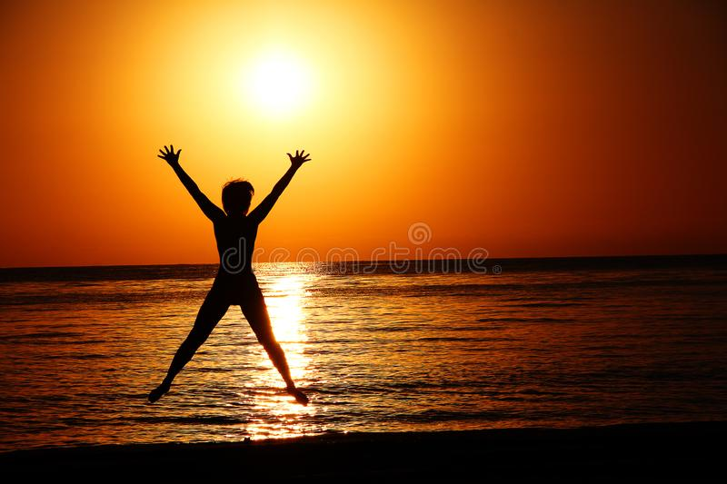 Silhouette of a jumping woman against the background of the setting sun over the sea. stock photos