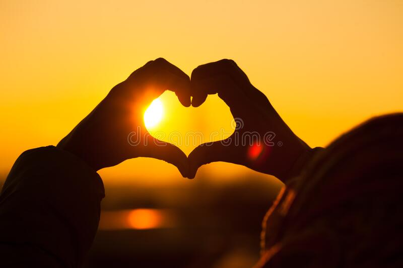 Silhouette of a kid making heart with hands stock photo