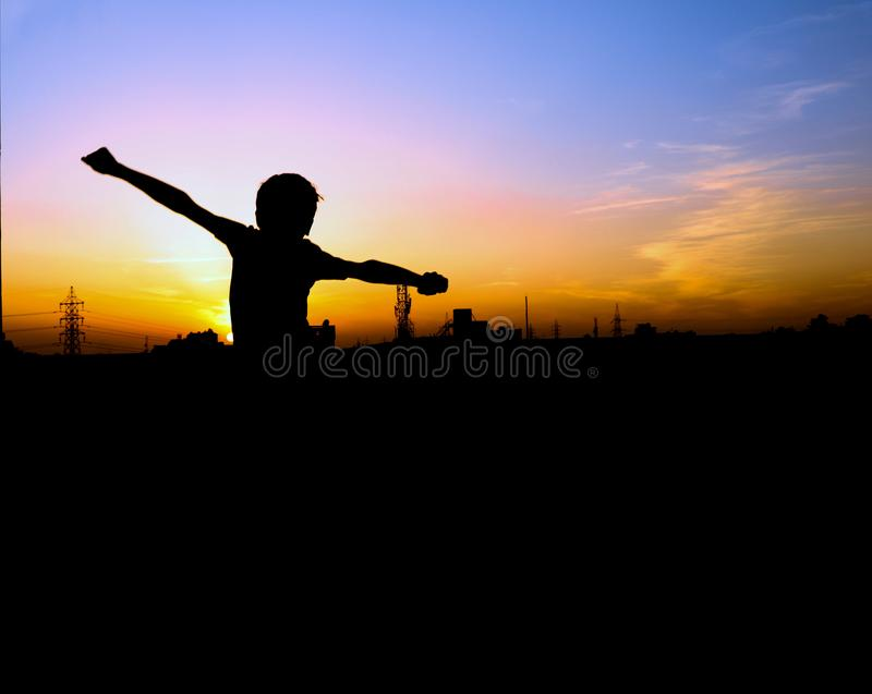 Happy boy jumping in front of sunset, people silhuette royalty free stock images