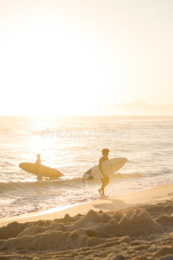 silhouette of kids walking along the beach with surfboards during sunset in Rio de Janeiro royalty free stock image