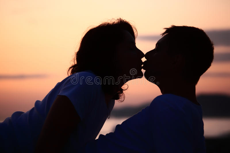 Silhouette kissing man and woman on beach royalty free stock images