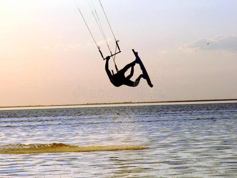 Silhouette of a kitesurf. A flying above water of a gulf royalty free stock photo